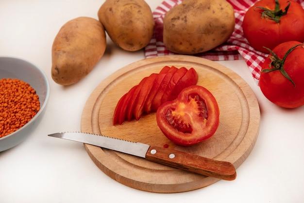 Draufsicht von rot geschnittenen tomaten auf einem hölzernen küchenbrett mit messer mit orangefarbenen linsen auf einer schüssel mit ganzen tomaten und kartoffeln lokalisiert auf einem karierten tuch auf einer weißen wand