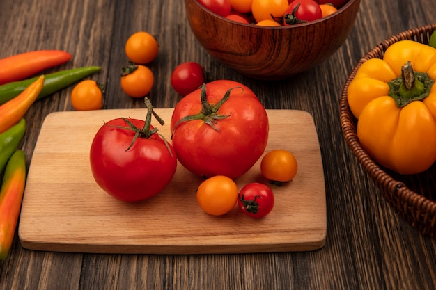 Draufsicht von roten großen tomaten auf einem hölzernen küchenbrett mit kirschtomaten auf einer hölzernen schüssel und paprika auf einem eimer auf einer hölzernen oberfläche