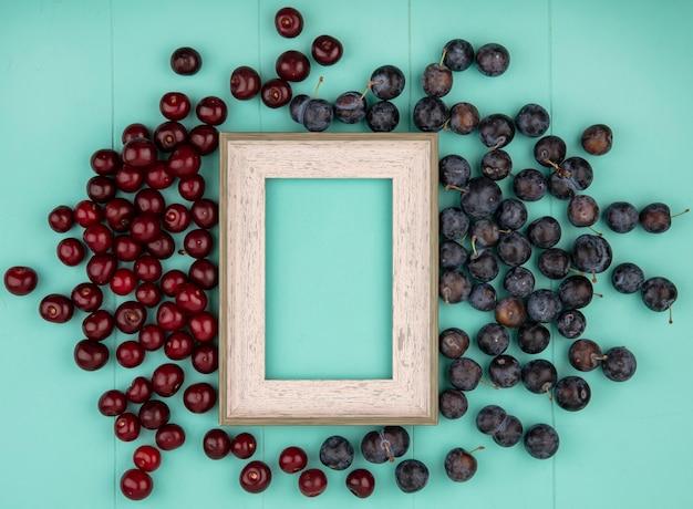 Draufsicht von roten köstlichen kirschen mit dunkelvioletten schlehen auf einem blauen hintergrund mit kopienraum