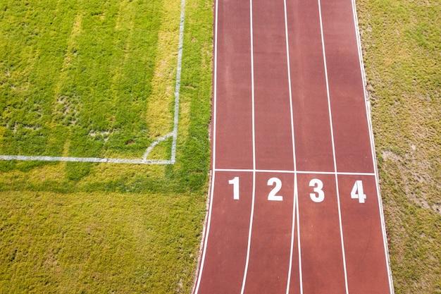 Draufsicht von roten laufbahnen und von rasen des grünen grases. infrastruktur für sportliche aktivitäten.