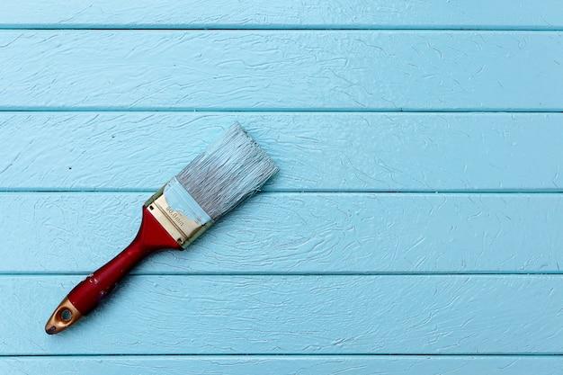 Draufsicht von roten pinseln auf blauer pastellfarbe des hölzernen brettes. objekt oder tapete konzept.