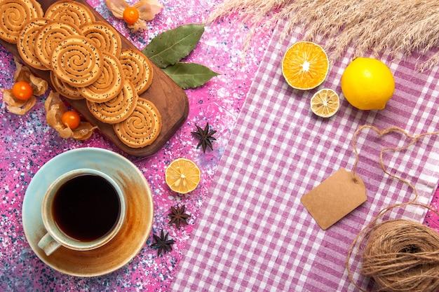 Draufsicht von runden süßen keksen mit tasse tee und zitrone auf der rosa oberfläche
