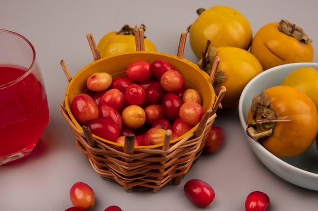 Draufsicht von säuerlichen süßen kornelkirschenfrüchten auf einem eimer mit kaki-früchten auf einer schüssel mit frischem kornelkirschenfruchtsaft in einem glas auf einer grauen oberfläche