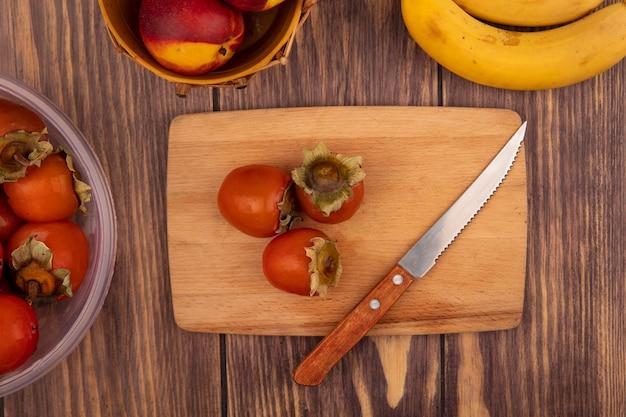 Draufsicht von saftigen kakis auf einem hölzernen küchenbrett mit messer mit pfirsichen auf einem eimer mit bananen lokalisiert auf einem hölzernen hintergrund