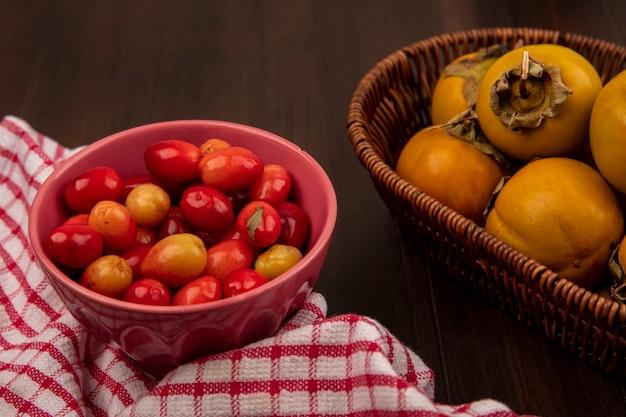 Draufsicht von saftigen kornelkirschen auf einer schüssel auf einem rot karierten tuch mit kakifrüchten auf einem eimer auf einer holzoberfläche