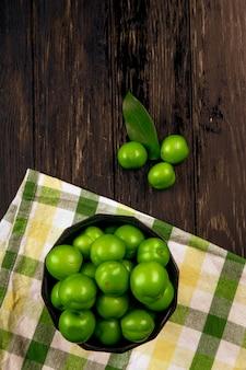 Draufsicht von sauren grünen pflaumen in einer schüssel auf karierter serviette auf dunklem holztisch