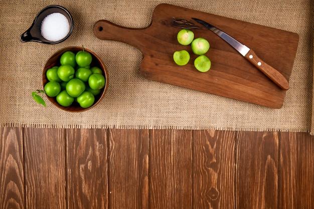 Draufsicht von sauren grünen pflaumen in einer schüssel und geschnittenen pflaumen auf einem hölzernen schneidebrett mit messer und salz auf sackleinen auf dunklem rustikalem tisch mit kopienraum