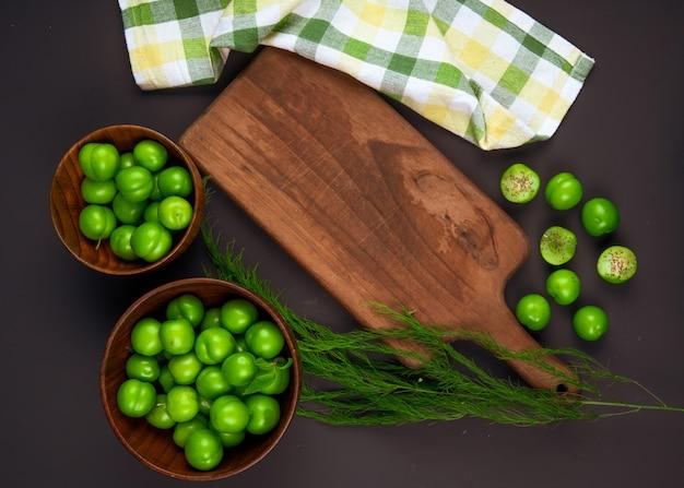Draufsicht von sauren grünen pflaumen in holzschalen und einem hölzernen schneidebrett mit karierter serviette auf schwarzem tisch