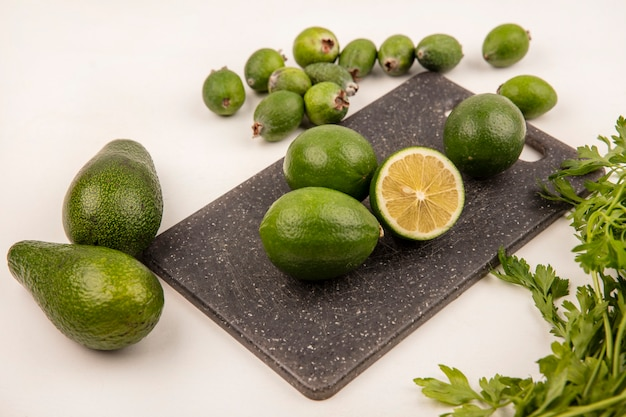 Draufsicht von sauren limetten auf einem küchenbrett mit feijoas und avocados lokalisiert auf einer weißen wand