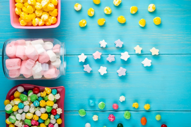 Draufsicht von schalen mit verschiedenen bunten bonbons und sternförmigem marshmallow, die von einem glasglas auf blauem hintergrund verstreut werden