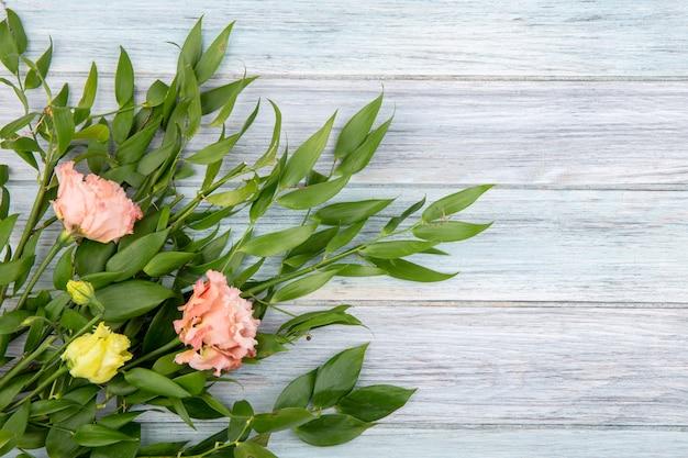 Draufsicht von schönen blumen wie rosa pfingstrosen und gelben rosen mit grünen blättern auf holz mit kopienraum