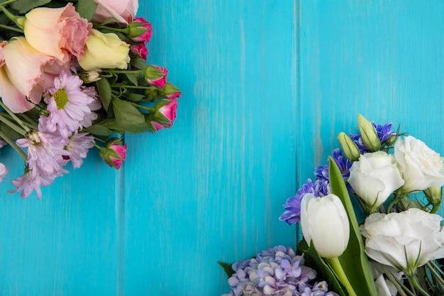 Draufsicht von schönen bunten blumen wie lila rosentulpe mit blättern auf einem blauen hintergrund mit kopienraum
