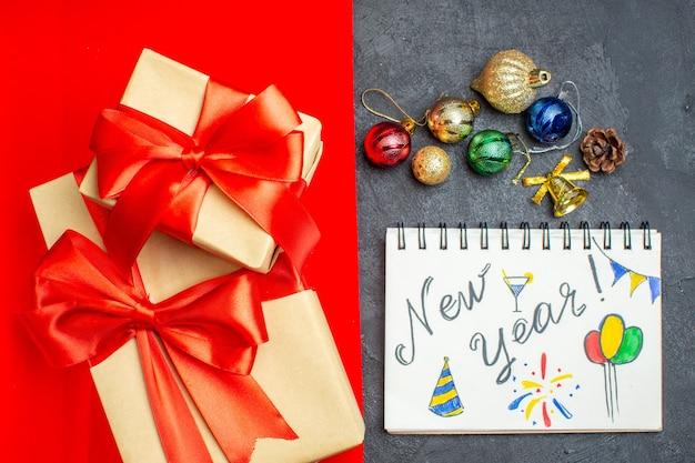 Draufsicht von schönen geschenken mit bogenförmigem banddekorationszubehörnotizbuch mit neujahrsschrift und zeichnungen auf einem roten und schwarzen hintergrund