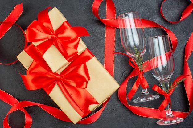 Draufsicht von schönen geschenken und glasbechern auf dunklem hintergrund