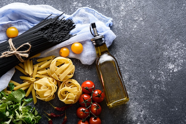 Draufsicht von schwarzen nudeln, fettuccine, tomaten, maissalat und flasche olivenöl auf schwarzem hintergrund, italienisches abendessen. nudelkonzept mit kopierraum