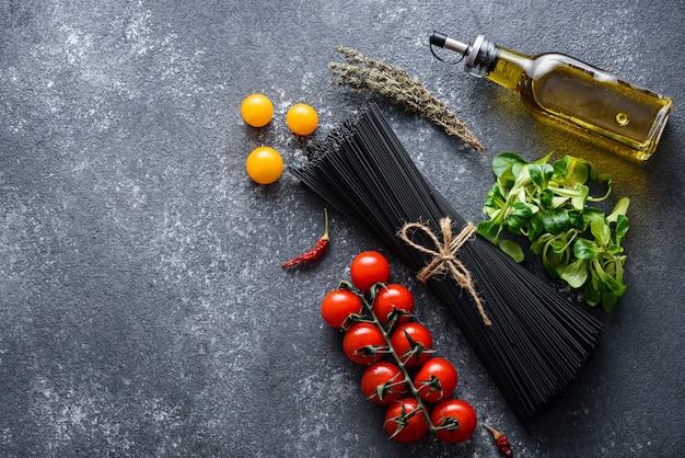 Draufsicht von schwarzen nudeln, tomaten, olivenöl, salat, chilischoten auf grauem hintergrund mit kopienraum, kochendes abendessenkonzept