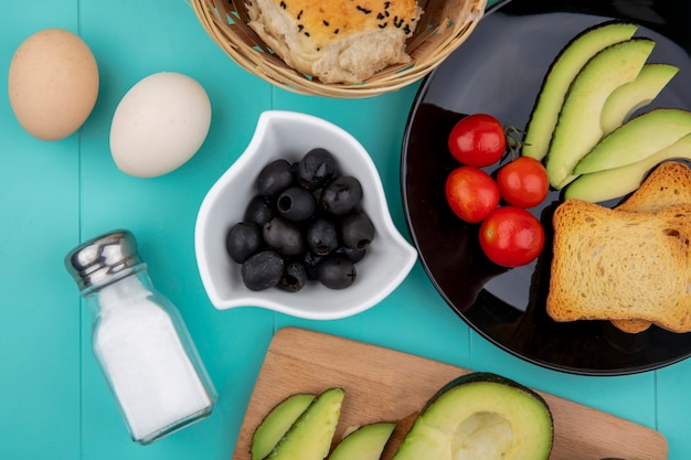 Draufsicht von schwarzen oliven auf weißer schüssel mit gemüse wie tomaten-avocado-scheibe auf schwarzem teller und einem eimer brot auf blau