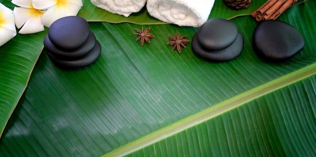 Draufsicht von schwarzen steinen und von tüchern für massagen auf grünen bananenblättern