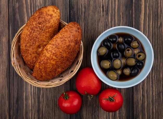 Draufsicht von schwarzen und grünen oliven auf einer blauen schüssel mit pastetchen auf einem eimer mit tomaten lokalisiert auf einem hölzernen hintergrund