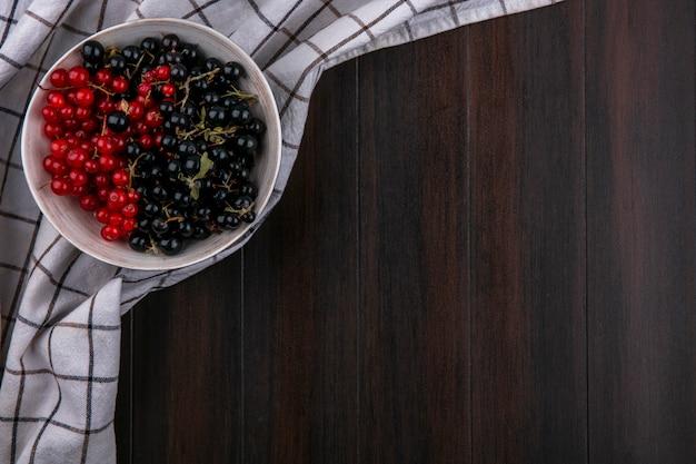 Draufsicht von schwarzen und roten johannisbeeren in einer schüssel auf einem karierten handtuch auf einer holzoberfläche