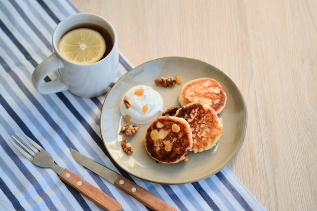 Draufsicht von selbst gemachtem käsepfannkuchen syrniki mit sauerrahm und tasse tee