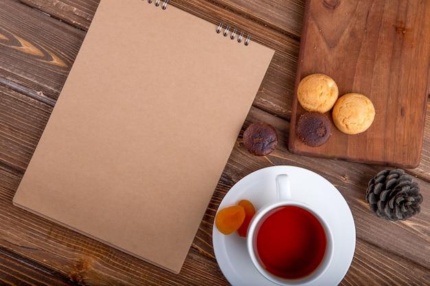 Draufsicht von skizzenbuchplätzchen und einer tasse tee mit zimtstangen auf hölzernem hintergrund