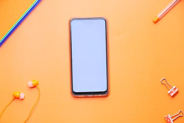 Draufsicht von smartphone und büro stationär auf orange hintergrund