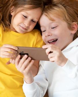 Draufsicht von smiley-kindern, die smartphone zusammen verwenden