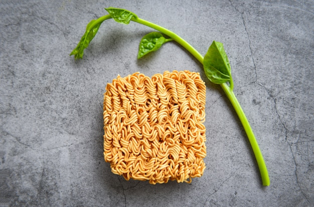 Draufsicht von sofortigen nudeln und von gemüse auf der dunklen ungesunden ernährung der nudel-thailändischen ungesunden fertigkost oder des schnellimbisses