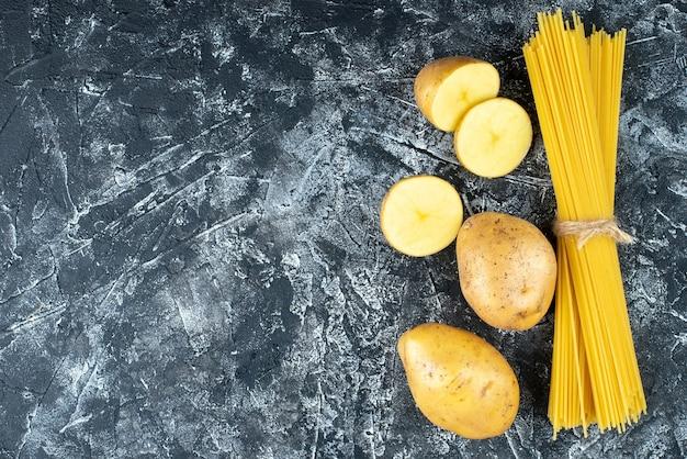 Draufsicht von spaghetti mit kartoffeln auf hellgrauer oberfläche
