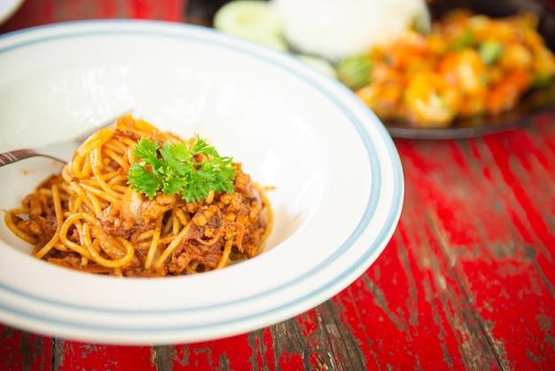 Draufsicht von spaghettis mit ketschup und schweinekotelett auf holztisch