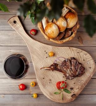 Draufsicht von steakscheiben auf knochen mit meersalz besprüht, kirschtomate