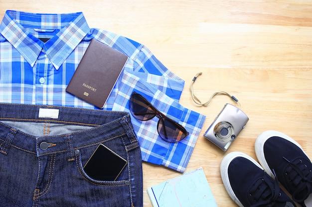 Draufsicht von stilvoller kleidung der frauen-mode des reisezubehörs auf hölzernem tabellenhintergrund, planend für reise des sommerferienkonzeptes