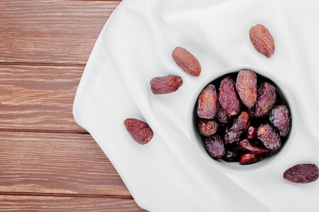 Draufsicht von süßen getrockneten dattelfrüchten in einer schüssel auf weißer tischdecke auf hölzernem hintergrund mit kopienraum
