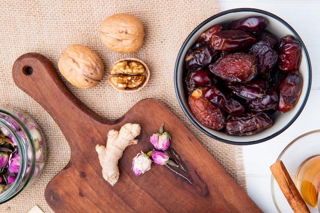 Draufsicht von süßen getrockneten datteln in einer schüssel und einem hölzernen schneidebrett mit ingwer und rosenknospen auf sackleinen