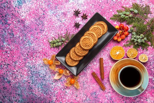 Draufsicht von süßen keksen in schwarzer form mit tasse tee und zimt auf hellrosa oberfläche