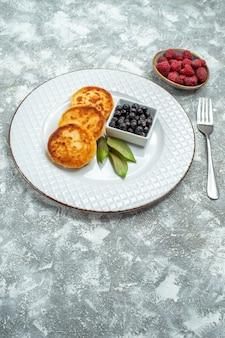 Draufsicht von süßen muffins mit beeren innerhalb platte auf der hellen oberfläche