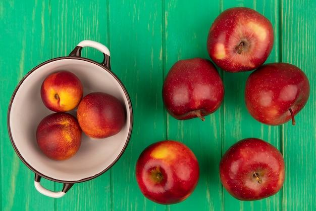 Draufsicht von süßen pfirsichen auf einer schüssel mit roten äpfeln lokalisiert auf einer grünen holzwand