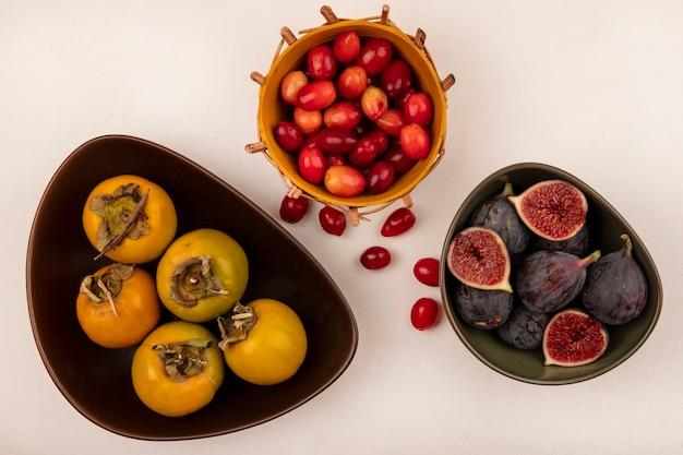 Draufsicht von süßen schwarzen feigen auf einer schüssel mit kornelkirschen auf einem eimer mit kaki-früchten auf einer schüssel auf einer weißen wand