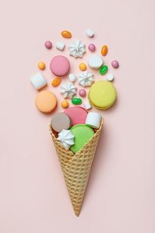 Draufsicht von süßigkeiten, die aus waffelkegel auf pastellrosa hintergrund verschütten