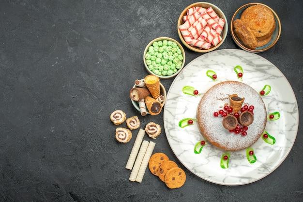 Draufsicht von süßigkeiten ein kuchen mit beerengrünsauceplätzchenbonbons