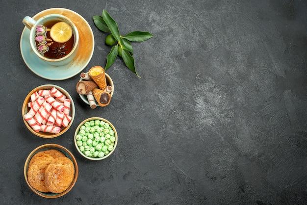 Draufsicht von süßigkeiten eine tasse teeplätzchen bunte süßigkeiten zitrusfrüchte mit blättern
