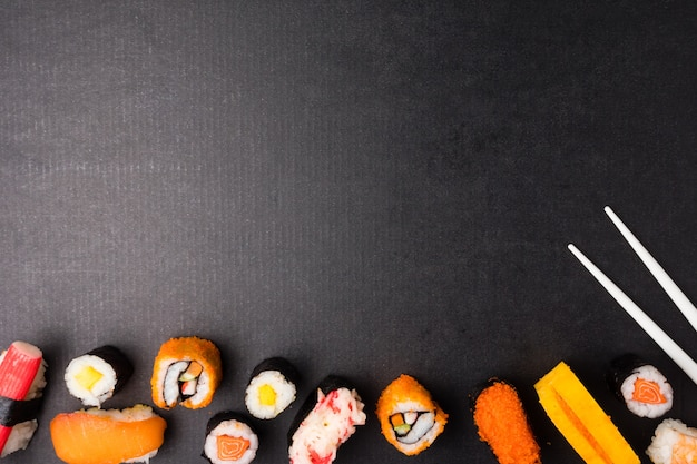 Draufsicht von sushi stellte und essstäbchen auf schwarzem hintergrund, japanisches lebensmittel ein.