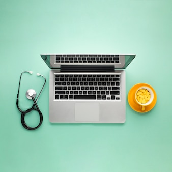 Draufsicht von tabletten auf schale mit laptop und stethoskop über grünem schreibtisch