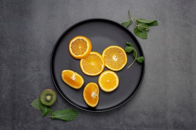 Draufsicht von tangerinenscheiben auf platte mit minze und kiwi