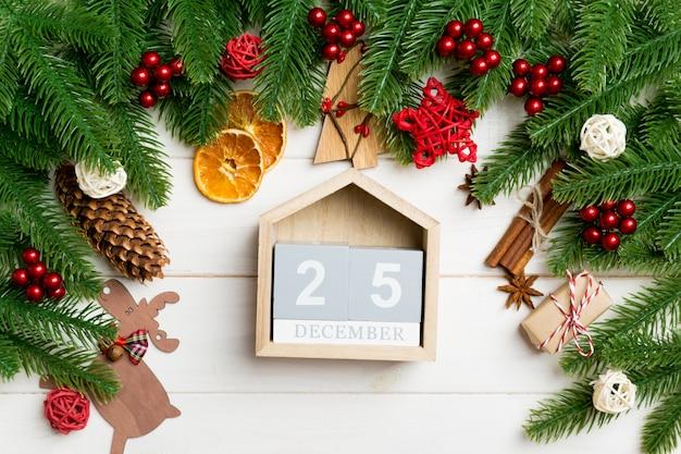 Draufsicht von tannenbaumasten auf holztisch. kalender mit festlichen spielsachen geschmückt. der fünfundzwanzigste dezember. weihnachtszeit-konzept