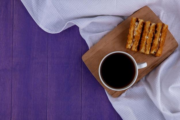Draufsicht von tasse kaffee und kuchen auf schneidebrett auf weißem stoff und lila hintergrund