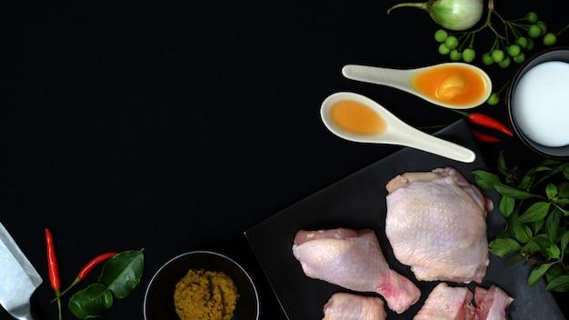 Draufsicht von thailändischen lebensmittelinhaltsstoffen und von gewürzen für hühnergrüncurry auf schwarzem hintergrund