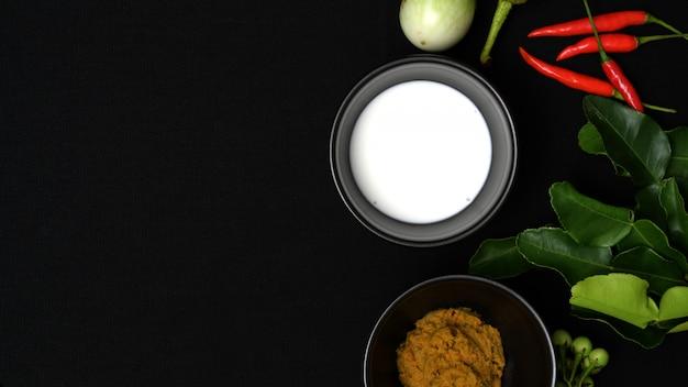 Draufsicht von thailändischen lebensmittelinhaltsstoffen und von gewürzen für hühnergrüncurry auf schwarzem schreibtisch