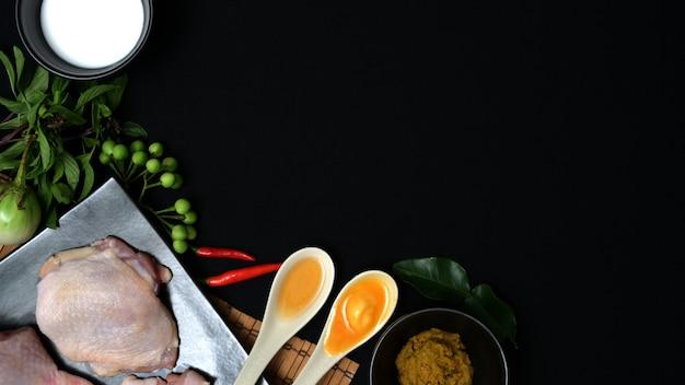 Draufsicht von thailändischen lebensmittelinhaltsstoffen und von kräutern für hühnergrüncurry auf schwarzem schreibtisch